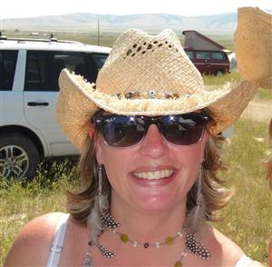 Headshot of Mrs. Roos wearing a straw hat and sunglasses